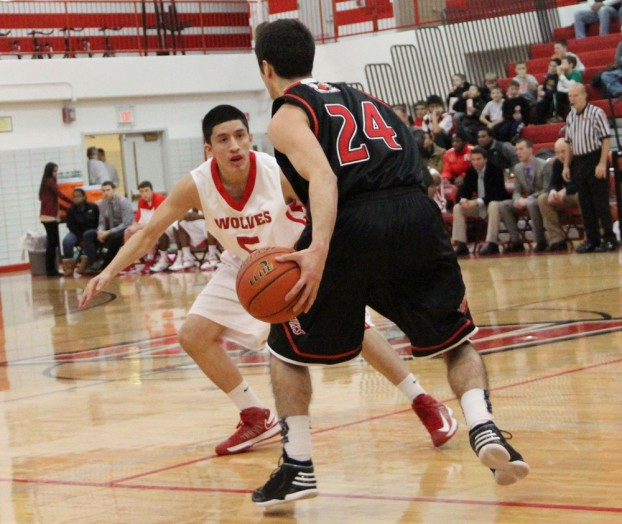 Senior Alfredo Gonzalez defends a Maine South ball handler during Friday's loss to the Hawks. Maine South won 50-29. PHOTO by Vinny Kabat