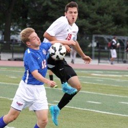 Senior Alen Radeljic attempts to steal the ball midair from Hoffman Estates midfielder in a game last season.