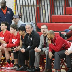 Boys' basketball head coach Bob Williams sits on the bench with his players as he coaches his final game against Evanston Tuesday, Feb. 28. Williams, who was placed on administrative leave earlier this week and is now back to his duties, is set to retire at the end of school year. Photo by Sana Kadir